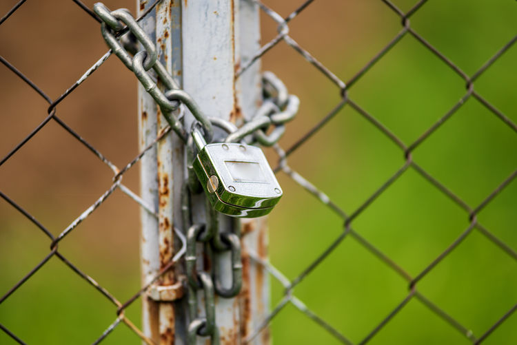 Old rusty heavy duty pad lock and chain on a fence and gate outdoors Security Protection Safety Chainlink Fence Fence Boundary Metal Focus On Foreground Barrier No People Close-up Lock Day Padlock Chain Outdoors Connection Wire Selective Focus Technology