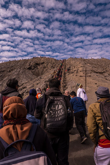 Rear view of people enjoying on mountain against sky