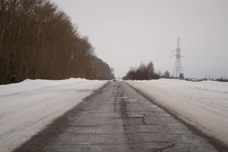 Long way home. Asphalt Cold Temperature Diminishing Perspective Electricity Pylon Gray Sky Long Nature Old Road Road Season  Sky Snow The Way Forward Tranquil Scene Tranquility Vanishing Point Winter