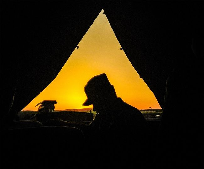 Silhouette man against yellow sky at night