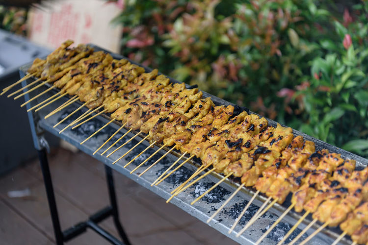 Preparation of the Satay dish Sticking Out Tongue Barbecue Barbecue Grill Close-up Day Food Food And Drink Freshness Grilled In A Row Meat On Sticks No People Preparing Food Satay Skewer