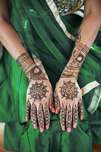 Close-up shot of Indian bride back hand with mehndi (henna tattoo) with beautiful sari in green lehenga Celebration Dress Green Color Hinduism India Indian Mehndi Ritual Tradition Wedding Bollywood Bride Ceremony Female Finger Hand Henna Lehenga Marriage  Religion Sangeet Saree Sari Tattoo Water