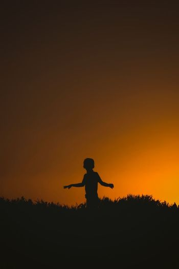 Silhouette boy standing on land against orange sky during sunset