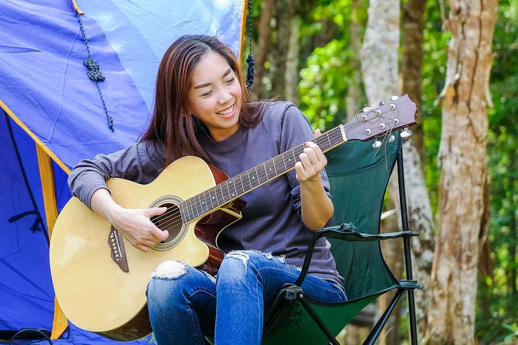 Smiling woman playing guitar while sitting by tent on chair at forest