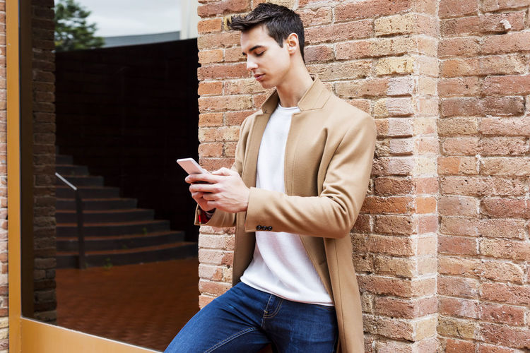 Young man using phone while standing by brick wall