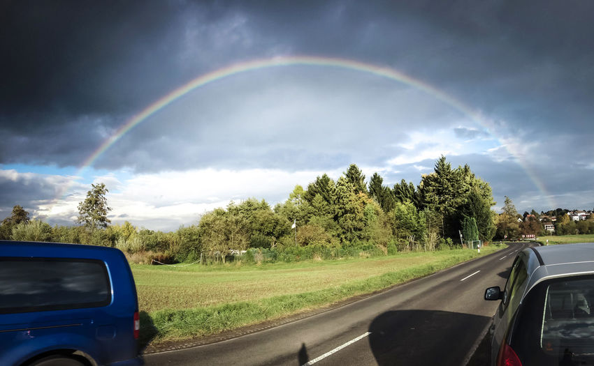 Rainbow over countryside road Rainbow Cloud - Sky Mode Of Transportation Motor Vehicle Car Rural Scene Land Sky No People Road Countryside Beauty In Nature Nature Land Vehicle Outdoors Field Overcast Day Scenics - Nature Natural Phenomenon