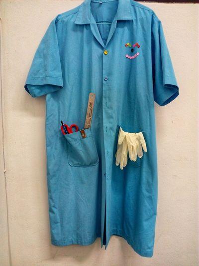 Blue uniform hanging against wall
