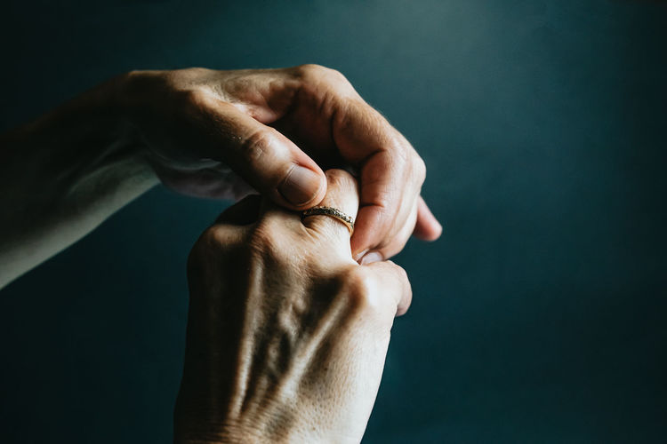 Cropped hand of woman holding wedding ring against colored background