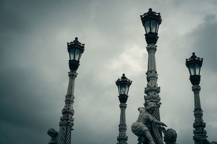 Intricate street lights with statues. Street Light Statue Lighting Equipment Monument Sculpture Outdoors Travel Destinations Architectural Column No People Silhouette Architecture Day Sky Cloud Rain