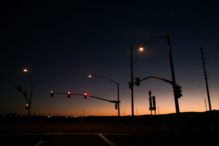 Silhouette Stoplights Against Sky During Sunset