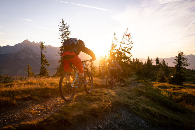 People riding bicycle on mountain against sky during sunset