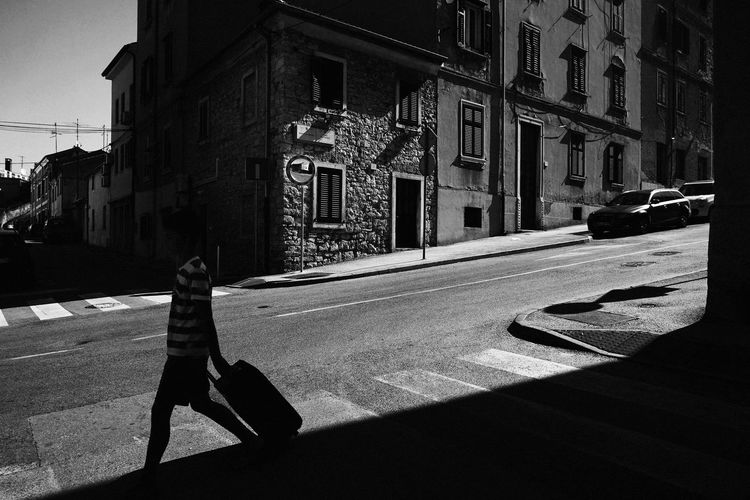 Shadow of person on street amidst buildings in city