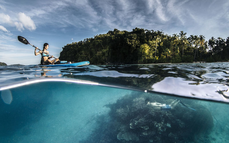 Woman paddleboarding and man snorkeling in sea against sky