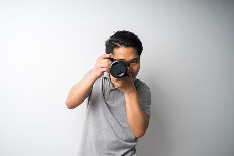 Midsection of man photographing against white background