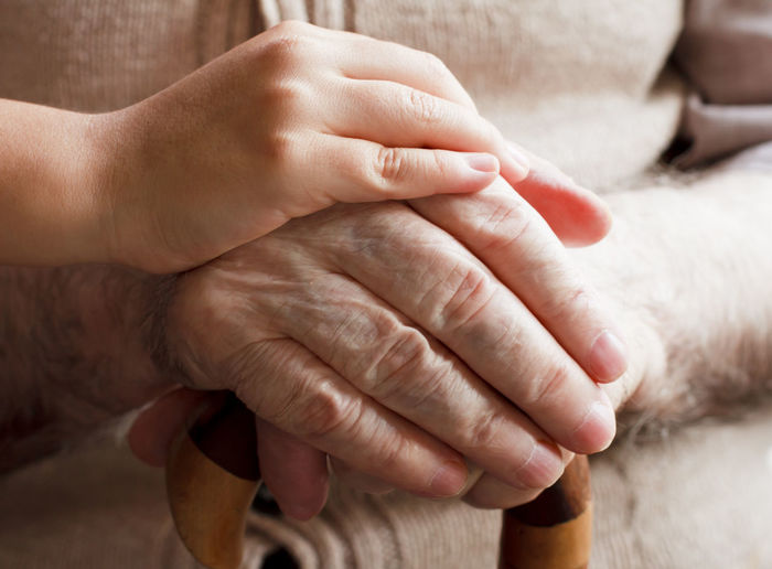 Close-Up Of Hand Consoling Senior Man