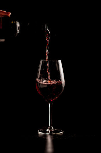 Wine glass on table against black background