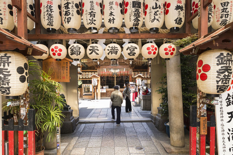 The entrance of a shinto shrine with colorful japanese paper lanterns at the nishiki market in Kyoto, Japan. Picture taken in May 2016. Chinese Lantern Japan Japan Photography Japanese Culture Market Shinto Shrine Shrine Shrine Of Japan Spirituality Travel Built Structure City Kyoto Lantern Lifestyles Nishiki Non-western Script Real People Rear View Religion Religion And Beliefs Script Text Travel Destinations Walking