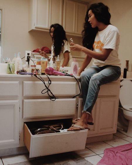 Woman sitting on cabinet with beauty products in bathroom
