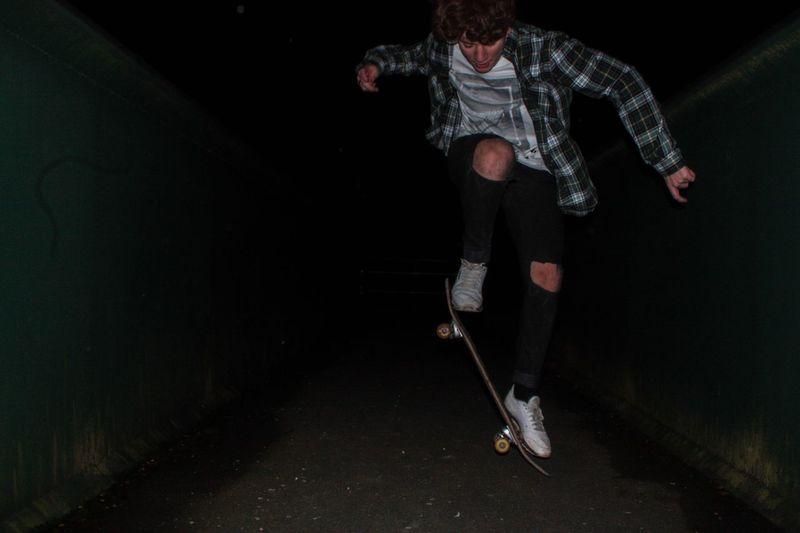 Teenage boy skateboarding on street in dark