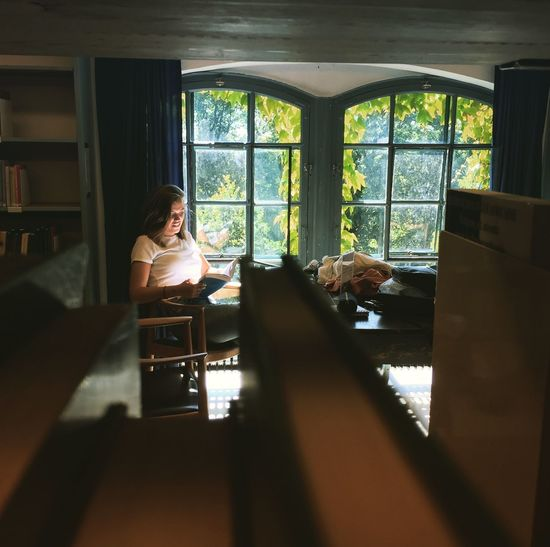 Woman sitting on table by window