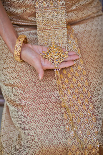 Bride in Thai traditional dress, Thai bridal gown One Person Human Hand Human Body Part Hand Pattern Midsection Close-up Women Adult Indoors  Lifestyles Jewelry Floral Pattern Holding Fashion High Angle View Real People Art And Craft Body Part Nail Finger Thai Bridal Gown Traditional Clothing Gold Colored