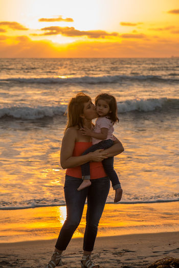 Young grandmother with her granddaughter by the ocean, enjoying some togetherness Beach Beauty In Nature Childhood Elementary Age Full Length Grandmother And Grandchild Idyllic Leisure Activity Lifestyles Mother And Child Mother And Daughter Nature Orange Color Scenics Sea Shore Standing Sunset Surf Togetherness Tranquil Scene Tranquility Vacations Water Wave