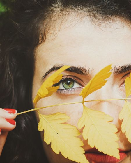 Close-up portrait of woman holding autumn leaves