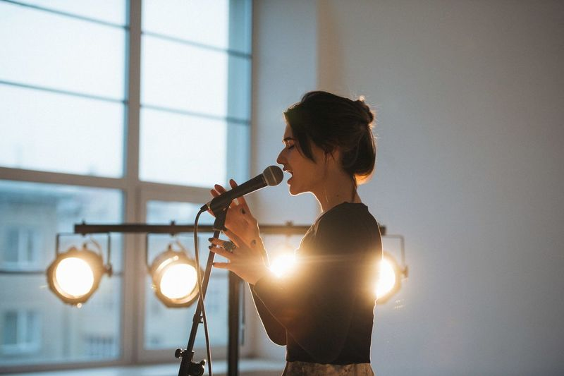 Side view of young woman singing indoors