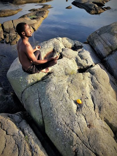 Side view of shirtless young man meditating while sitting on rock at beach