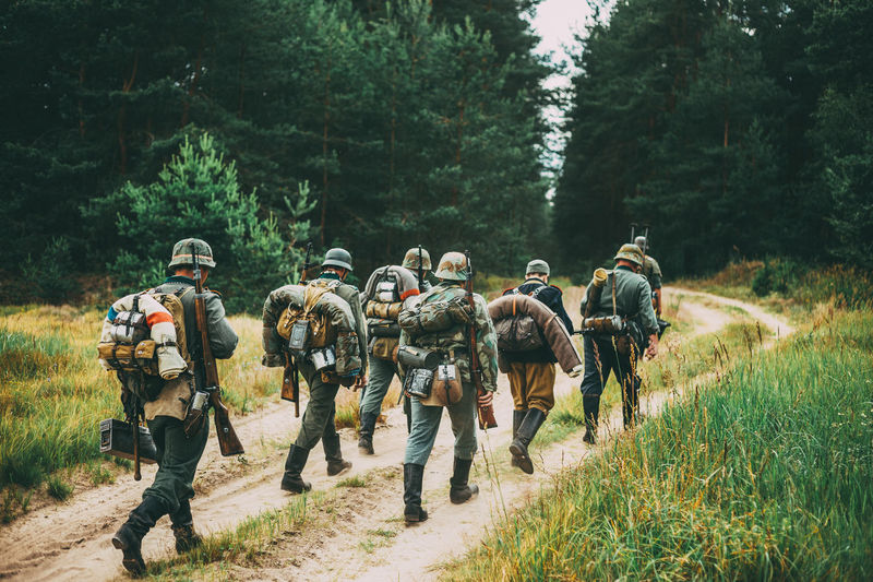 Group Of Unidentified Re-enactors Dressed As German Soldiers Marching Along Forest Road. Summer Season. War Ww2 WWII Ww1 Front Army Soldier Millitary Forest Uniform German Road Ussr Tree Weapon Walking Gun Re-enactors Marching