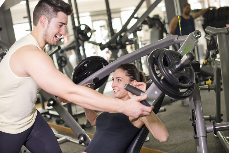 Woman exercising by trainer on equipment in gym