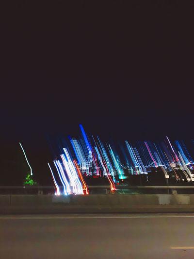 Illuminated lights in city against sky at night