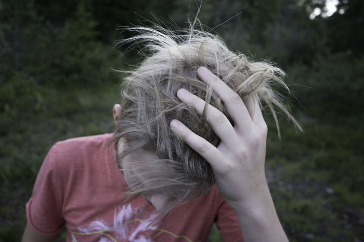 Close-up of boy with hand in hair on field