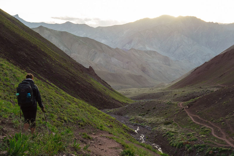 Rear View Of Backpacker Standing On Mountain During Sunset