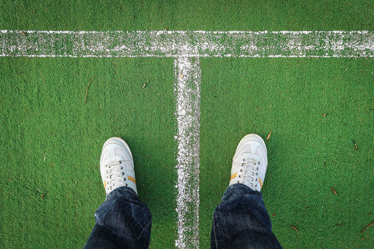 Low Section Of Man Standing On Soccer Field