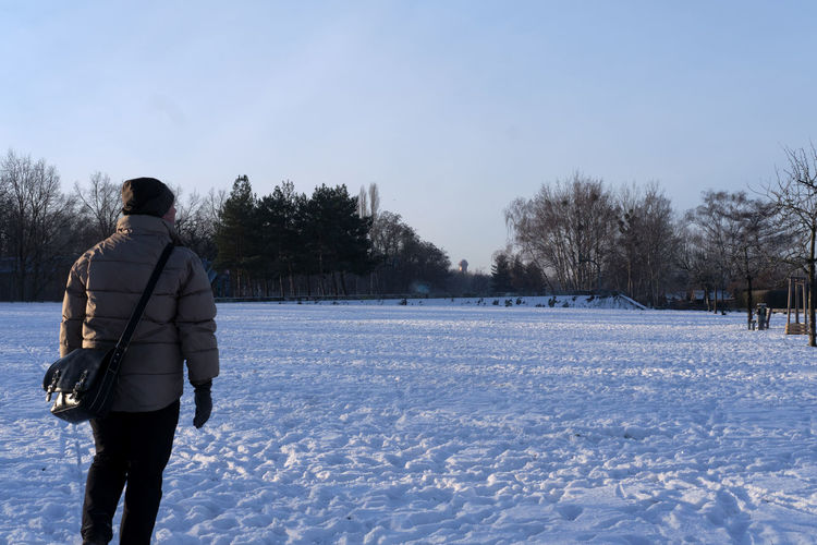 Rear view of man on snow field against sky