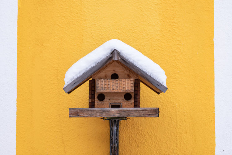 Close-up of wooden birdhouse on yellow wall. snow covered roof.