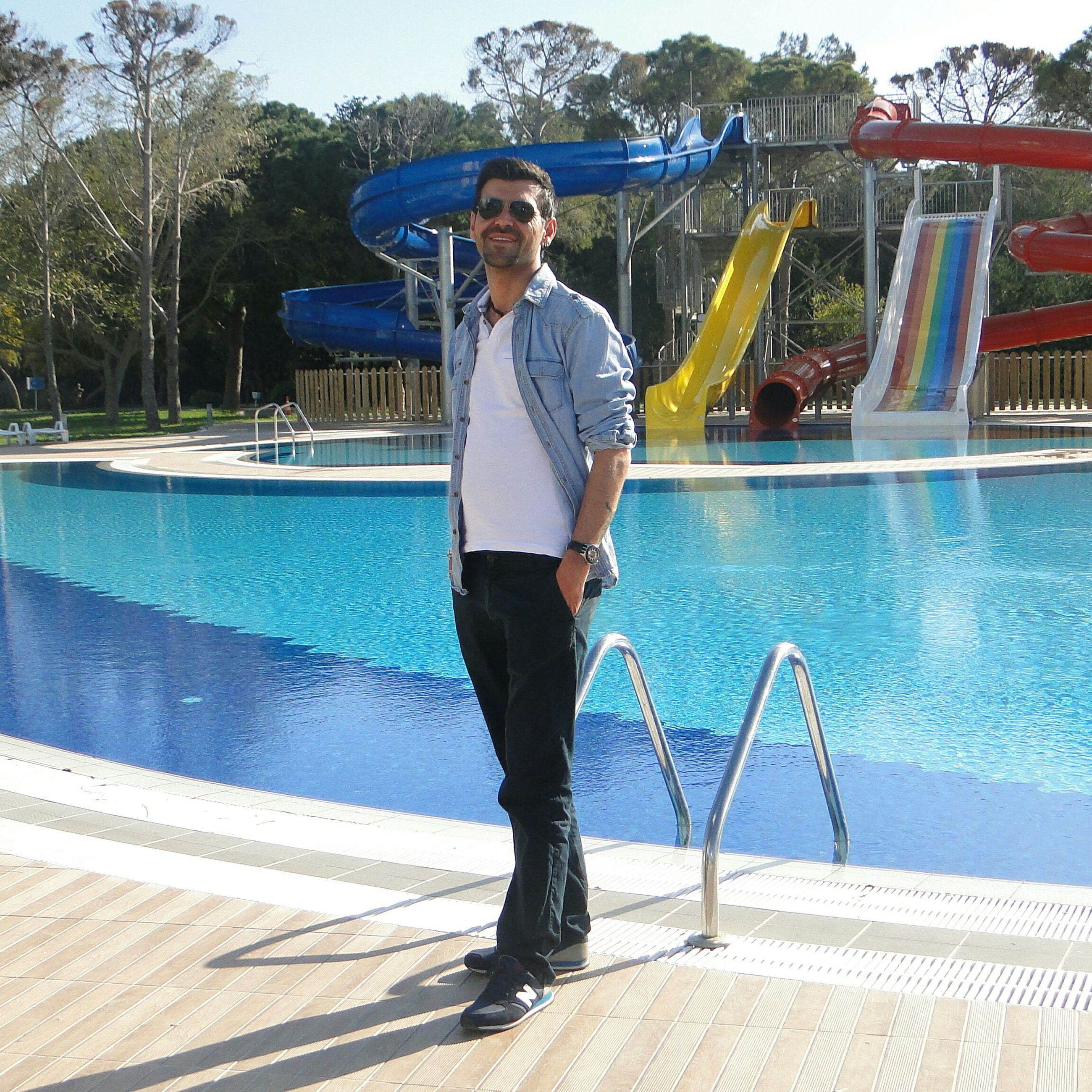 young adult, person, full length, lifestyles, casual clothing, looking at camera, water, leisure activity, portrait, front view, sunglasses, young men, standing, built structure, smiling, railing, building exterior