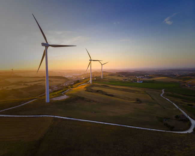 Alternative Energy Beauty In Nature Environment Environmental Conservation Field Fuel And Power Generation Land Landscape Nature No People Outdoors Renewable Energy Road Rural Scene Scenics - Nature Sky Sunset Sustainable Resources Technology Turbine Wind Power Wind Turbine