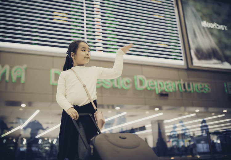 Low angle view of girl with luggage standing in airport
