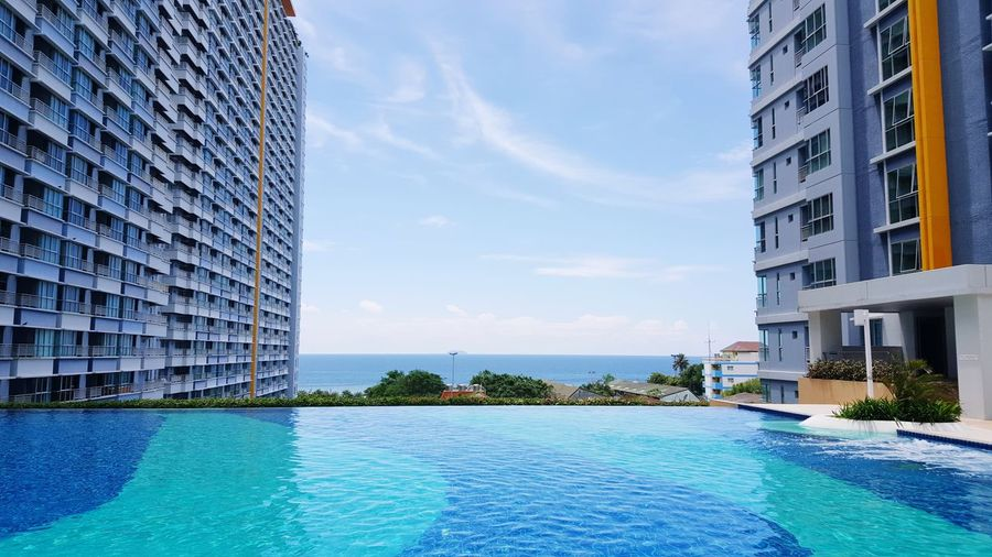 Swimming pool and sea by buildings in city against sky