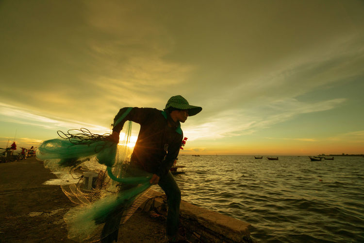 Fisherman throwing net in sea against sky during sunset