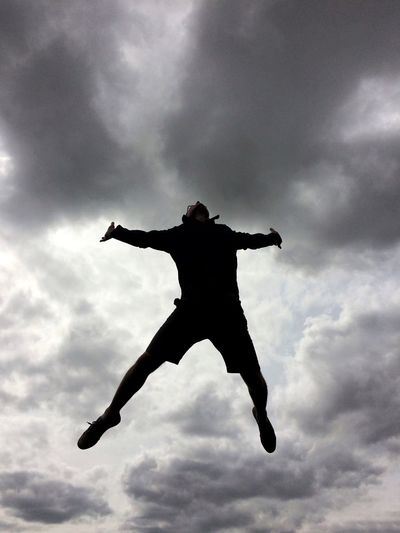 The silhouette of a man jumping high in the air with a dark, stormy sky behind in a pain or freedom concept image. Sky Cloud - Sky Silhouette Mid-air Low Angle View Jumping One Person Energetic Outdoors Freedom Free Spirit Joy Leap Of Faith Leaping Fall Falling Float Floating Outstretched Arms Storm Storm Cloud Pain Blackandwhite Black And White High The Week On EyeEm Rethink Things Be. Ready. Black And White Friday Black And White Friday