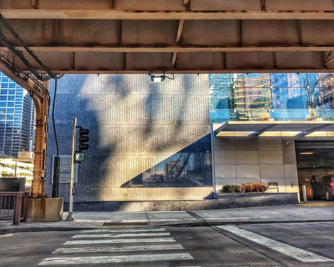 Reflection and shadow of scene from river behind the photographer, cast on a building's exterior on Chicago's Lake Street. Waysofseeing Underneath Cityscape Concrete Chicago River Drawbridge  Drawbridge Up Chicago El Streetlights Stoplight Crosswalk Pedestrian Walkway Texture Building Exterior Awning Glass Shadows Reflection Chicago Loop Downtown Chicago Chicago Lake Street Elevated Train Elevated Track Architecture Built Structure Building Exterior City Mobility In Mega Cities Colour Your Horizn