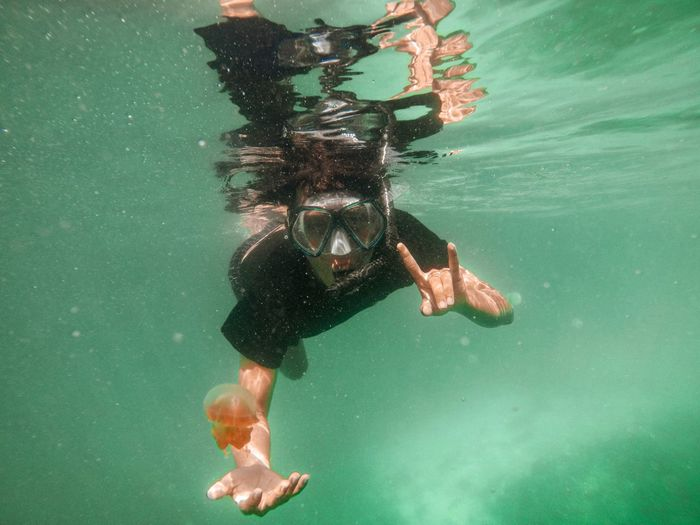 Man swimming in sea with jellyfish