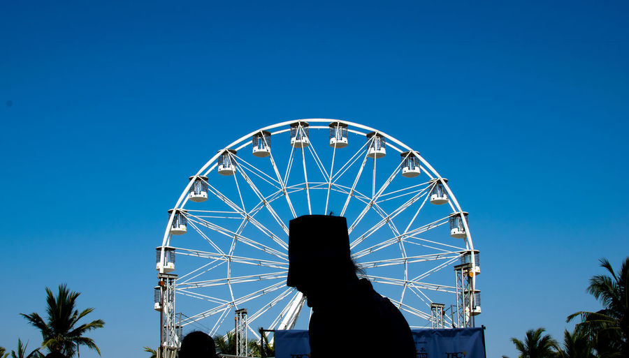 Low angle view of silhouette ferris wheel against clear blue sky