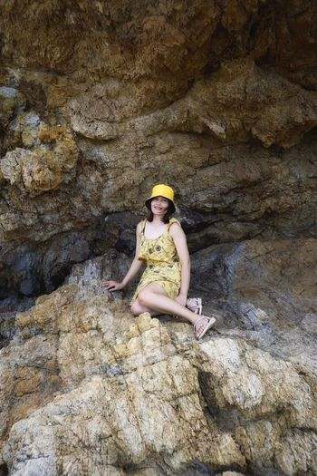 Full length portrait of woman sitting on rock