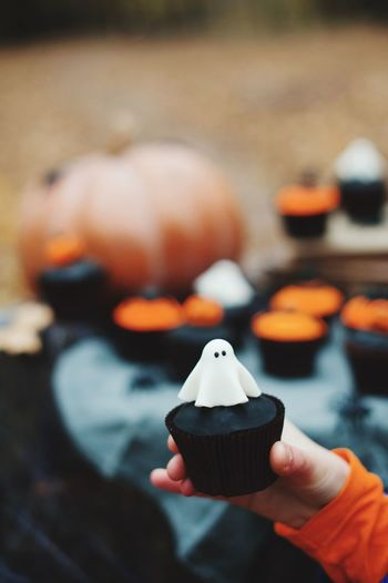 cupcakes on Halloween Human Hand Hand Real People Holding Human Body Part Focus On Foreground One Person Hot Drink Lifestyles Food Sweet Food Close-up Body Part Orange Color Food And Drink Unrecognizable Person Finger Freshness Drink