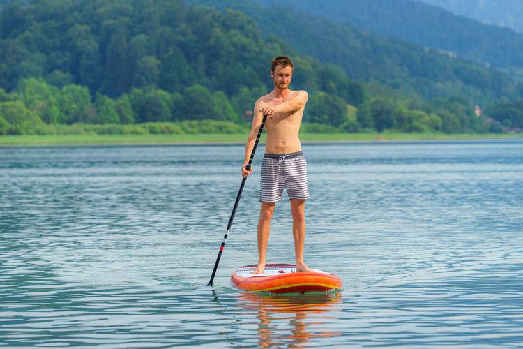 Full length of shirtless man paddleboarding on lake