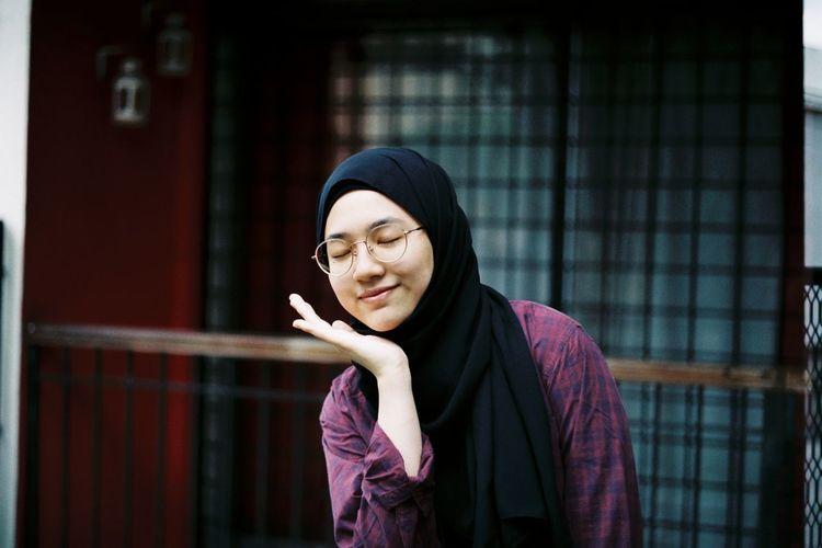 Teenage girl wearing hijab and eyeglasses with closed eyes
